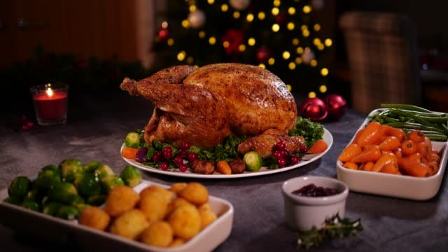 4k dolly: christmas turkey dinner / lunch with christmas tree - cena natale video stock e b–roll