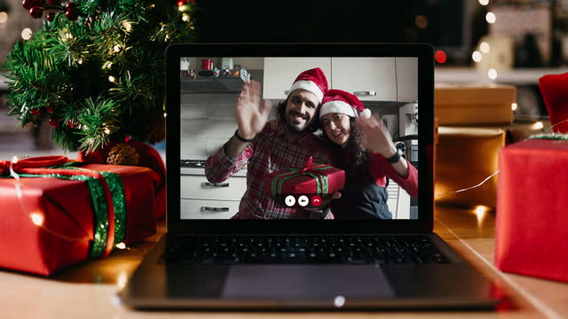 Christmas video call on a laptop screen at home Christmas video call on a laptop screen at home. Millennial man and woman celebrating Christmas respecting social distancing. They are looking at camera. New normal during Coronavirus Covid-19 pandemic concept. holiday stock videos & royalty-free footage
