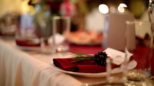 christmas wedding banquet hall interior details with decorand table setting at restaurant. winter season decoration of bulb garlands, candles, flowers, cones and fir tree branches - arredamento video stock e b–roll