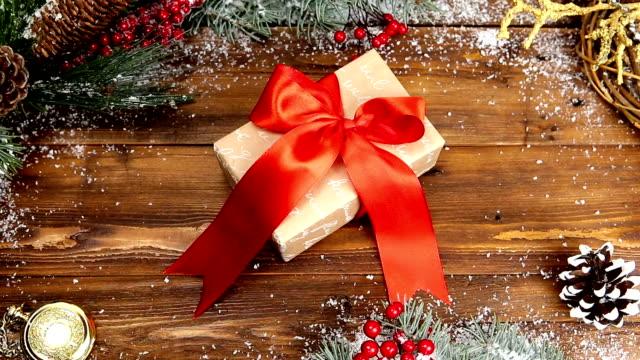 christmas trä bakgrund med snöiga gren ovanifrån. en gåva med en röd rosett på ett träbord - blue yellow band bildbanksvideor och videomaterial från bakom kulisserna