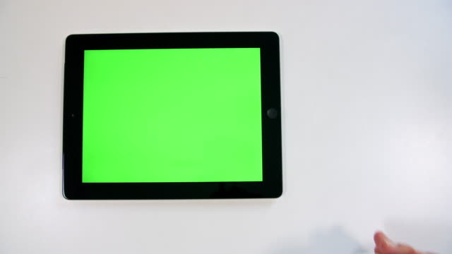 Chroma key tablet screen 4K color footage of an unrecognisable person working with a green screen tablet computer. table top view stock videos & royalty-free footage