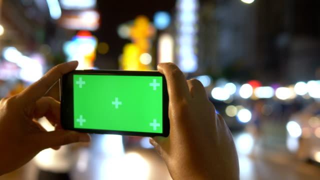 vídeos de stock e filmes b-roll de chroma key : women holding smartphone on night city - fotografar