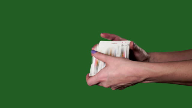 Chromakey. Green screen. Women's hands interfere with a deck of cards and throw them.