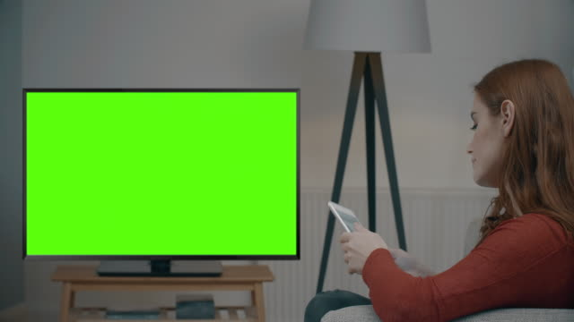 Chromakey TV, tablet and credit card. Over shoulder shot of a beautiful young woman holding and using her digital tablet and credit card, she is sitting on a sofa in a modern living room, occasionally looking up to look at the Chromakey TV screen. Space for your message in the television screen. DS. watching tv stock videos & royalty-free footage