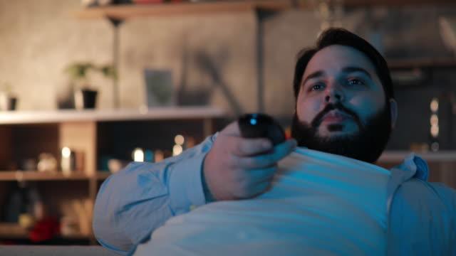 chubby man changing channels  in living room - samotność filmów i materiałów b-roll