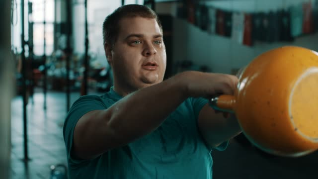 Chubby man doing exercise with kettlebell Chubby man doing exercise with kettlebell at gym gym health club stock videos & royalty-free footage