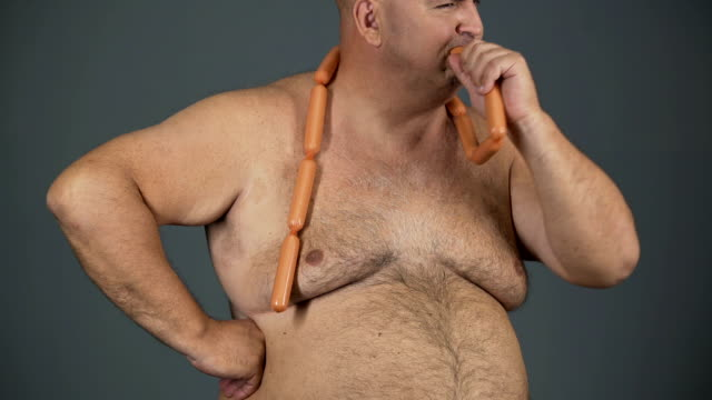 Chubby man eating sausages with appetite, food addiction, risk of diabetes video