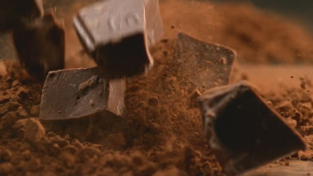chunks of chocolate falling into powdered chocolate - cioccolato video stock e b–roll