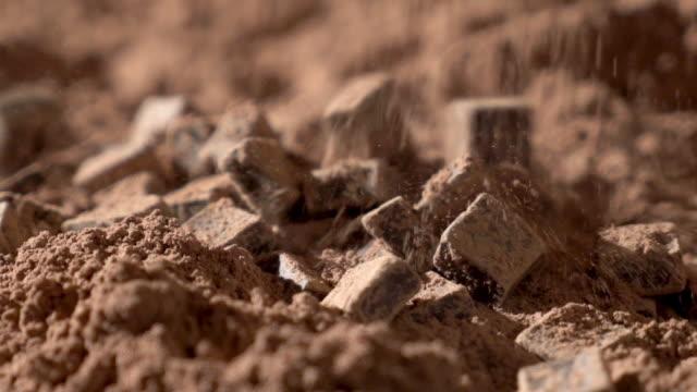 vídeos de stock e filmes b-roll de chunks of chocolate splashing in cocoa powder slow motion - cacau em pó