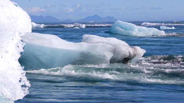 Chunks of ice drifting out to the North Atlantic Ocean Chunks of ice drifting out to the North Atlantic Ocean near the Jokulsarlon glacial lagoon, Iceland icecap stock videos & royalty-free footage