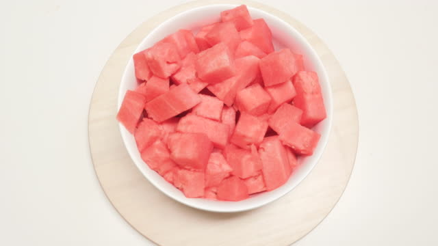 Chunks of Watermelon in a Ceramic Serving Bowl Spin on a Wooden Turntable Birds eye wide shot of chunks of watermelon in a ceramic serving bowl spin on a wooden turntable. The vegan snack is a fresh and healthy diet food. The bright red fruit is the perfect way to beat the summer heat. watermelon stock videos & royalty-free footage
