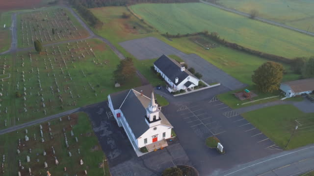 Church and cemetery at sunrise. Brodheadsville, Poconos region, Pennsylvania. Aerial drone video with the backward and tilting-up camera motion.