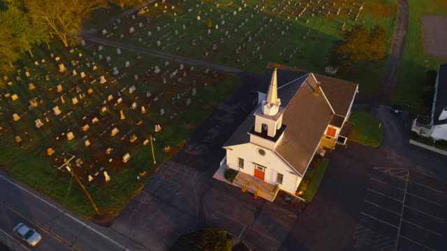 vídeos de stock e filmes b-roll de church and cemetery at sunrise. brodheadsville, poconos region, pennsylvania. aerial drone video with the forward and tilting-down camera motion. - igreja