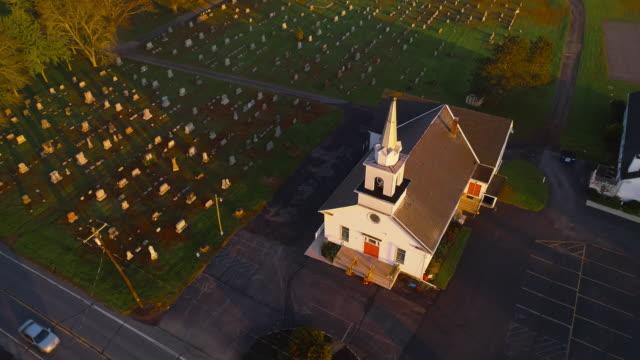 stockvideo's en b-roll-footage met kerk en begraafplaats bij zonsopgang. brodheadsville (regio poconos), pennsylvania. aerial drone video met de voorwaartse en kantelbare camerabeweging. - kerk