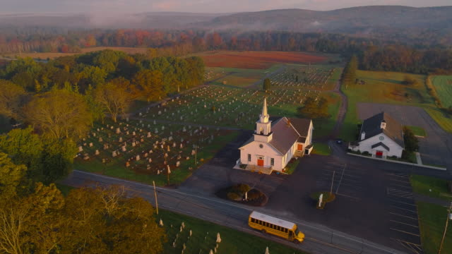 Church and cemetery at sunrise. Brodheadsville, Poconos region, Pennsylvania. Aerial drone video with the forward and tilting-down cinematic camera motion.