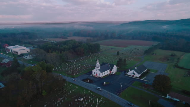 Church at sunrise. Brodheadsville, Poconos region, Pennsylvania. Accelerated time-laps-style aerial drone video with the orbit camera motion.