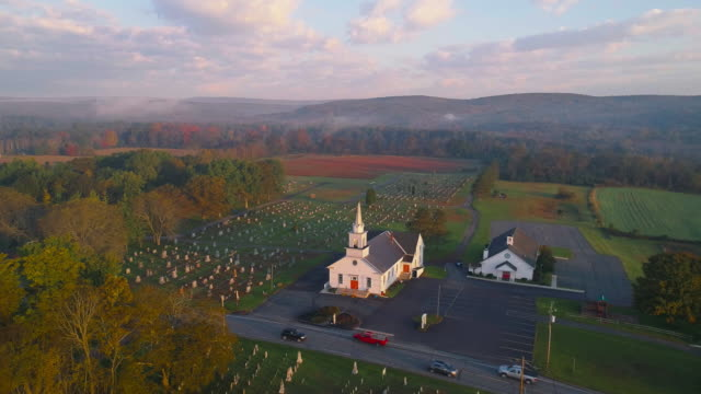 Church at sunrise. Brodheadsville, Poconos region, Pennsylvania. Morning traffic on Route 209. Aerial drone video with the static camera.
