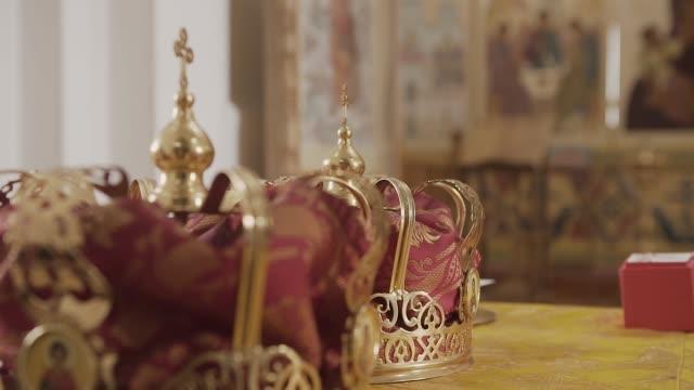 vídeos de stock e filmes b-roll de church attributes for wedding ceremony. gold crowns are on the altar - coroa