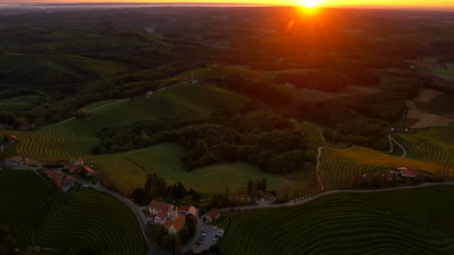 AERIAL Church In The Countryside At Dusk HD1080p: AERIAL shot of a church on top of a hill surrounded with vineyards in the sunset. Prekmurje. Slovenia. Also available in 4K resolution. cultivated land stock videos & royalty-free footage