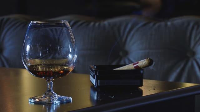cigar and cognac - puro stok videoları ve detay görüntü çekimi