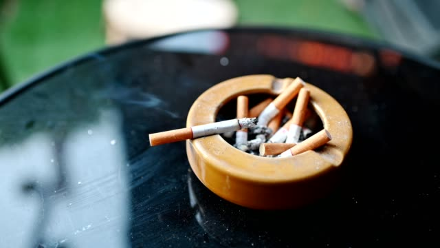 cigarette burning with smoking on ceramic ashtray - nicotina video stock e b–roll