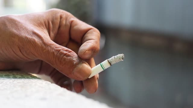 Cigarette in hand of a man. Cigarette in hand of a man. Closeup a cigarette holding in hand of a male. Smoking causes cancer and emphysema. Health Care concept. emphysema stock videos & royalty-free footage
