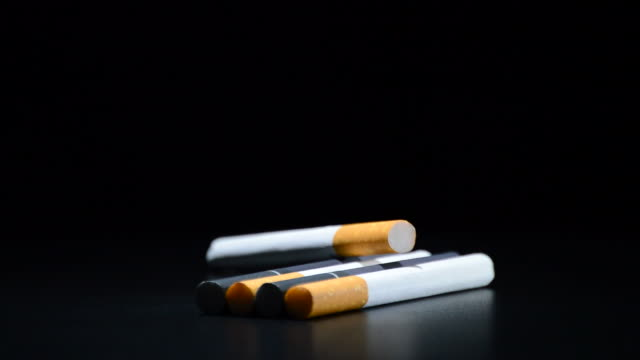 Cigarettes tobacco rotating on black background video