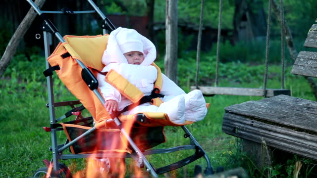 Cild sitting in front of the campfire in the pram video