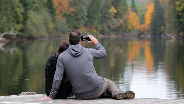 cinemagraph, vuxna par att ha kul på trä docka i hösten och tar bilder med mobiltelefon - flod vatten brygga bildbanksvideor och videomaterial från bakom kulisserna