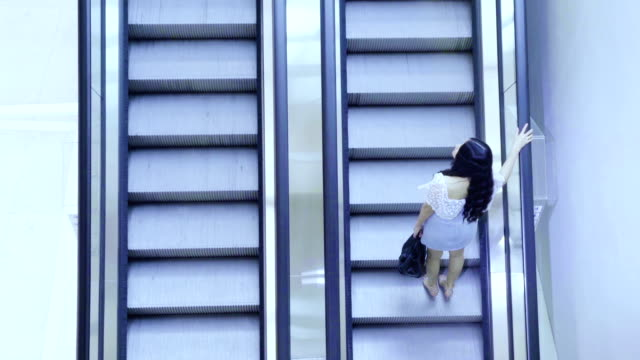 cinemagraph : asian women standing on the escalator - scala mobile video stock e b–roll