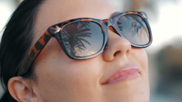 Cinemagraph - Beautiful young brunette smiling girl in retro sunglasses in the tropical vacation. Palm trees reflection in glasses. Travel concept. Slow motion video