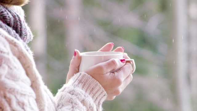 4K Cinemagraph close up of woman drinking hot chocolate and watching snow falling, slow motion