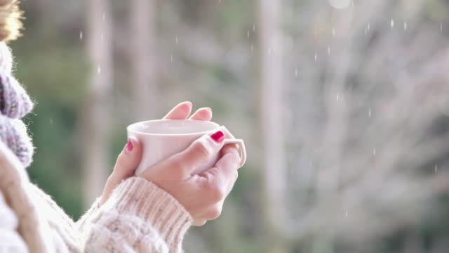 vídeos de stock, filmes e b-roll de 4k cinemagraph fechar mulher beber quente chocolate e ver neve caindo - chocolate quente