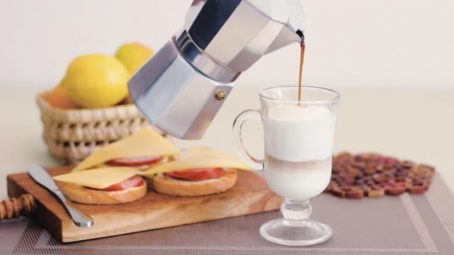 cinemagraph, coffee pouring from moka pot into tall glass with milk in home kitchen, making latte macchiato - francuska kuchnia filmów i materiałów b-roll