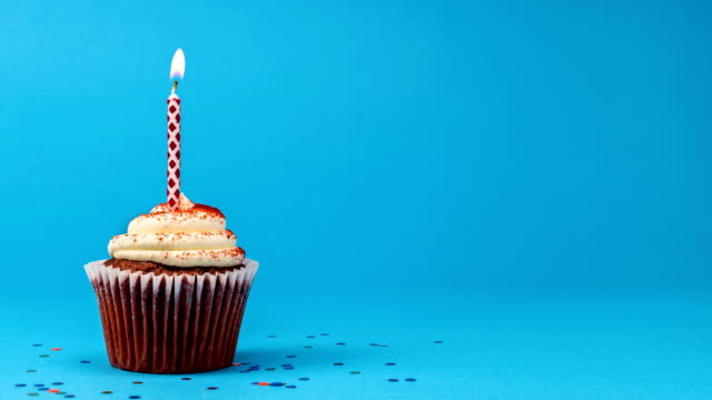Cinemagraph Cupcake Birthday Candle Seamless Loop Cinemagraph of a birthday red velvet cupcake with birthday candle burning on a blue background with confetti seamless looping background. happy birthday stock videos & royalty-free footage