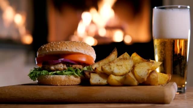 vídeos de stock e filmes b-roll de cinemagraph - hamburger with potata and beer on the fireplace background. - hambúrguer comida