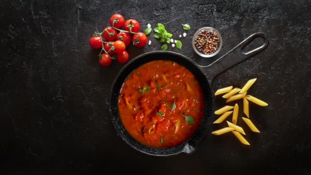 vídeos de stock e filmes b-roll de cinemagraph loop. cooking pasta penne with tomato sauce and basil on iron cast pan. - sauce tomatoes
