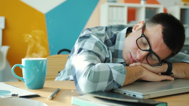vídeos de stock e filmes b-roll de cinemagraph loop of male employee sleeping on desktop in office with hot drink on table - dormitar