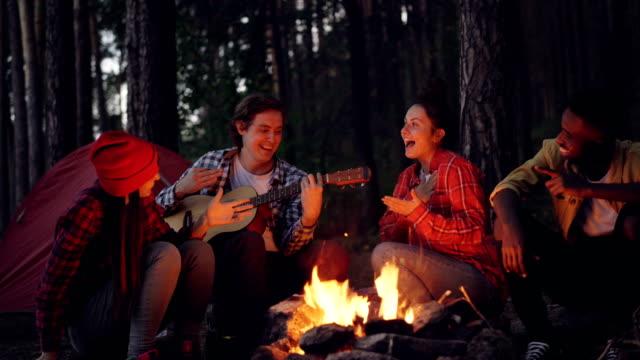 cinemagraph loop - ung man turist spelar gitarr medan sina vänner sjunger och skrattar sitter runt elden i trä på kvällen njuter av naturen och företaget. - bål utomhuseld bildbanksvideor och videomaterial från bakom kulisserna