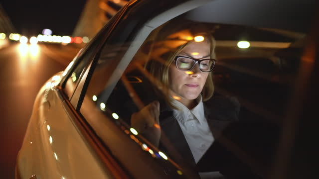 ws cinemagraph of a businesswoman using a tablet in a taxi - работа допоздна стоковые видео и кадры b-roll