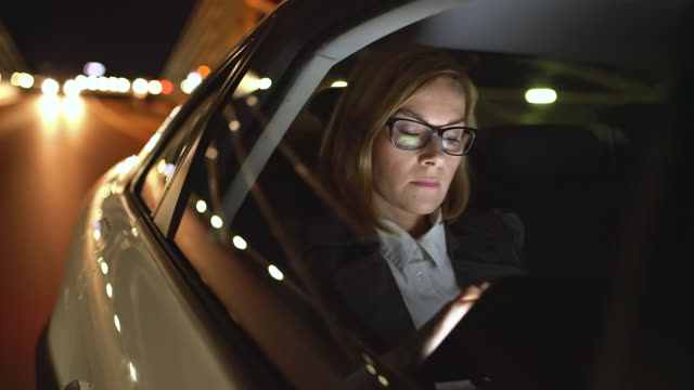 ws cinemagraph of a businesswoman using a tablet on the back seat of a car - business travel stock videos and b-roll footage