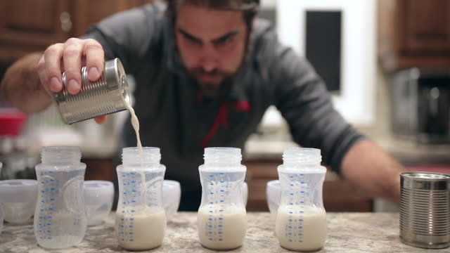 Cinemagraph of a Dad Preparing Baby Bottles Cinemagraph of a Dad Preparing Baby Bottles in the family kitchen feeding stock videos & royalty-free footage