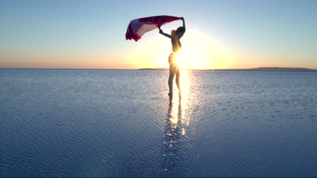 cinemagraph of beautiful dancer holding a canadian national flag on the lake. a windy day. - canada flag stock videos & royalty-free footage