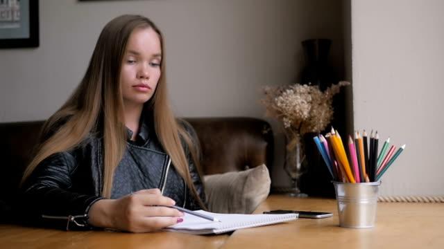 Cinemagraph de linda garota elaboração com lápis, copo de água e lápis coloridos na mesa de madeira, simulado, janela grande - vídeo