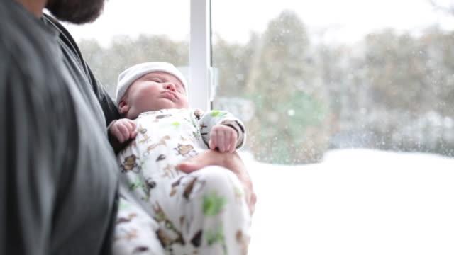 stockvideo's en b-roll-footage met cinemagraph van liefdevolle vader met pasgeboren baby dicht bij raam in de winter - family winter holiday
