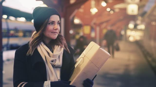 cinemagraph av kvinna med julklapp på tågstationen - waiting for a train sweden bildbanksvideor och videomaterial från bakom kulisserna