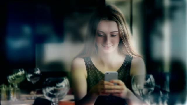 cinemagraph. telefon-meddelande i vinbaren. attraktiv ung kvinna. - telefonmeddelande bildbanksvideor och videomaterial från bakom kulisserna