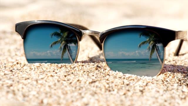 cinemagramm - sonnenbrille auf dem sand. bewegung-foto. - sonnenbrille stock-videos und b-roll-filmmaterial
