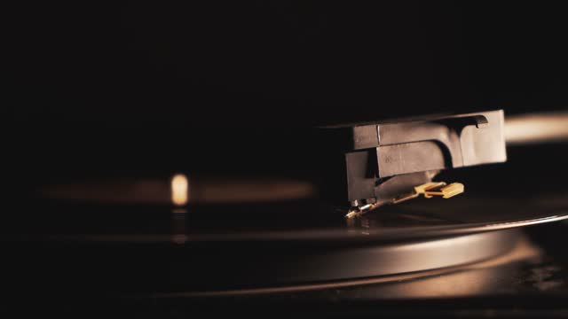 4K Cinemagraph vinyl record spinning close-up turning starting on a dark background. Close up of turntable tonearm playing. Retro-styled, old school