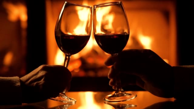 cinemagraph - young couple have romantic dinner with wine over fireplace background. - valentines day stock videos and b-roll footage